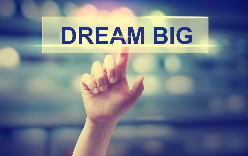Dream Big concept with hand pressing a button on blurred abstract background