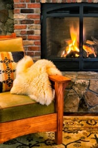 Chair by a stone and brick fireplace with a crackling fire. Cozy
